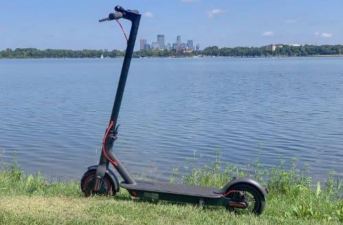 main skuter listrik di pantai dan rumput